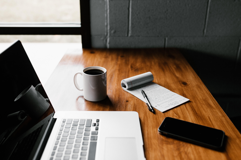 Laptop mit Block und Handy